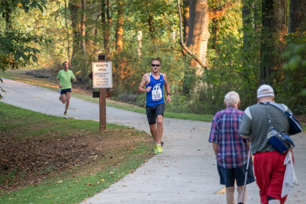 The GreenBelt trail is being used by two man walking while half-marathon runners are racing around the trails curve.